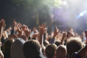 Rear view shot of a crowd enjoying a live concert with their hands raised